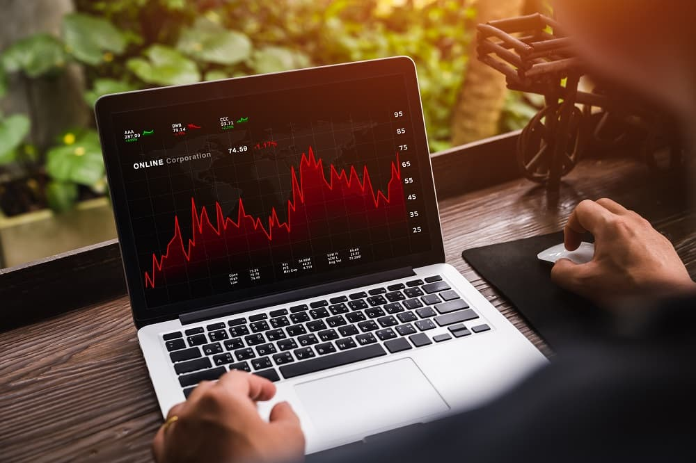 Businessman looking at daily trading prices on online stock market through laptop at home with graph showing on screen.