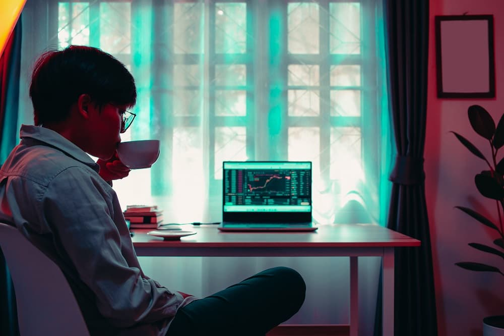 business Asian woman 30s looking graphs cryptocurrency trading platforms on laptop and drinking hot coffee with the calculator, notebook on the desktop table at on vivid colorful office home.
